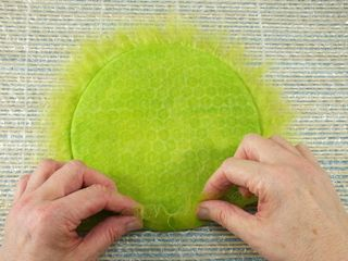 Fold fringe of wool over