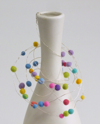 Bead hanger hooked into neck of vase